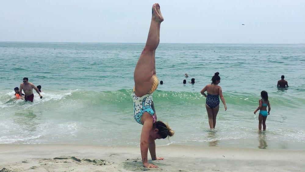 Victoria Caputo haciendo una parada de manos en la playa