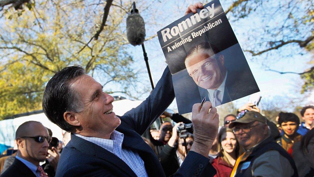 Mitt Romney sosteniendo un cartel de su padre, George Romney