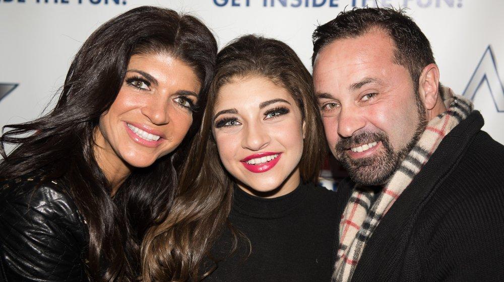 Teresa Giudice, Gia Giudice y Joe Giudice sonriendo y abrazándose en un evento de alfombra roja