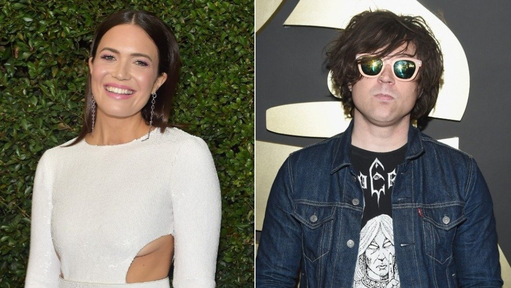 Imagen dividida de Mandy Moore en blanco y sonriente, y Ryan Adams en una chaqueta de mezclilla azul y gafas de sol con una expresión neutral