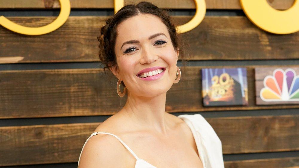 Mandy Moore con un traje blanco, sonriendo con el pelo recogido en un evento temático de This Is Us