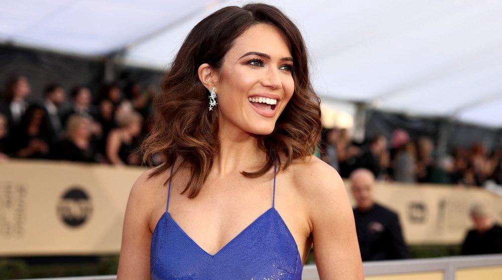 Mandy Moore con un vestido azul, sonriendo grande y mirando a un lado en los Premios SAG 2018