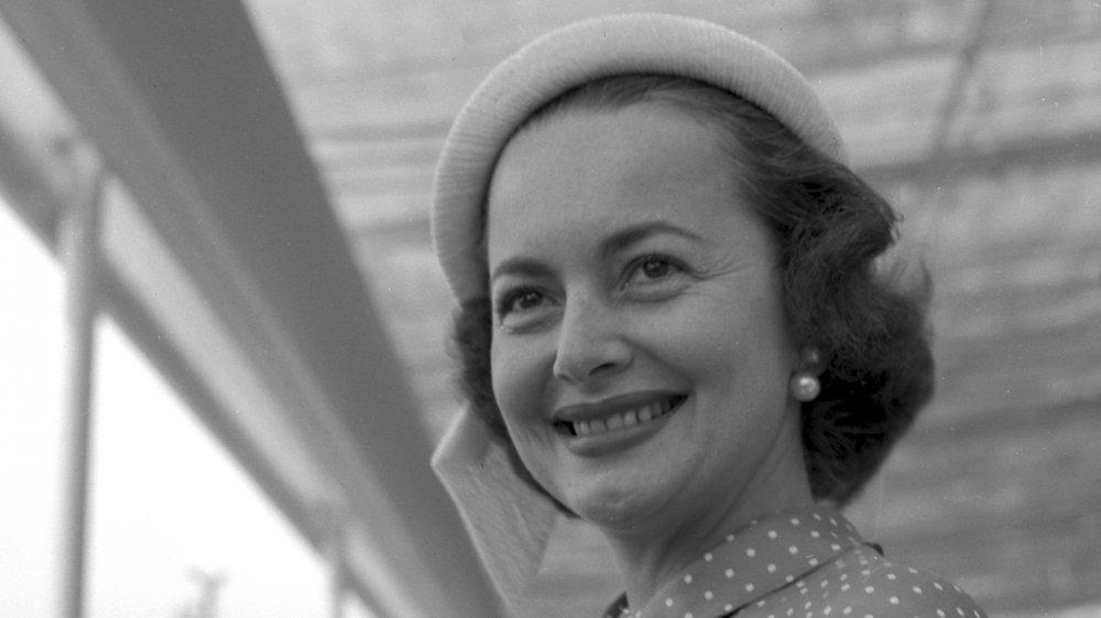 Foto en blanco y negro de Olivia de Havilland con un sombrero y aretes de perlas, sonriendo