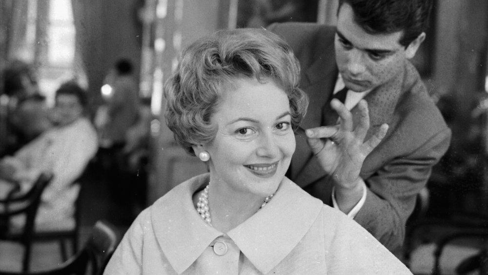Foto en blanco y negro de Olivia de Havilland sonriendo mientras se arregla el cabello