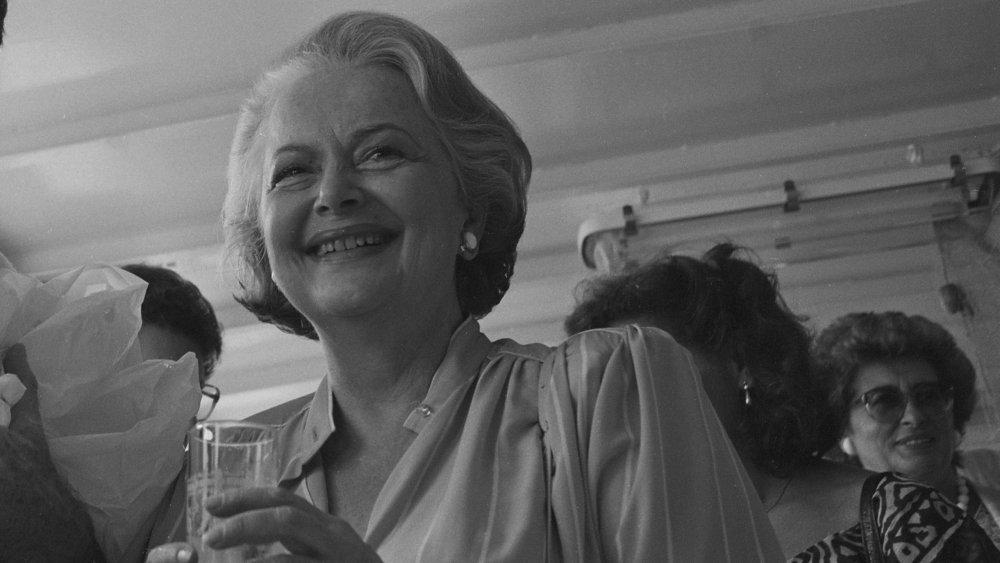 Foto en blanco y negro de Olivia de Havilland sonriendo y sosteniendo una copa