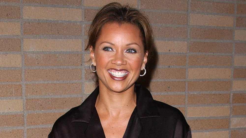 Vanessa Williams sonriendo frente a una pared de ladrillos