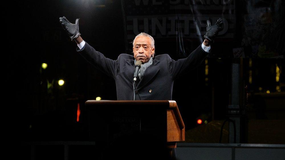 Al Sharpton con guantes negros con ambos brazos levantados