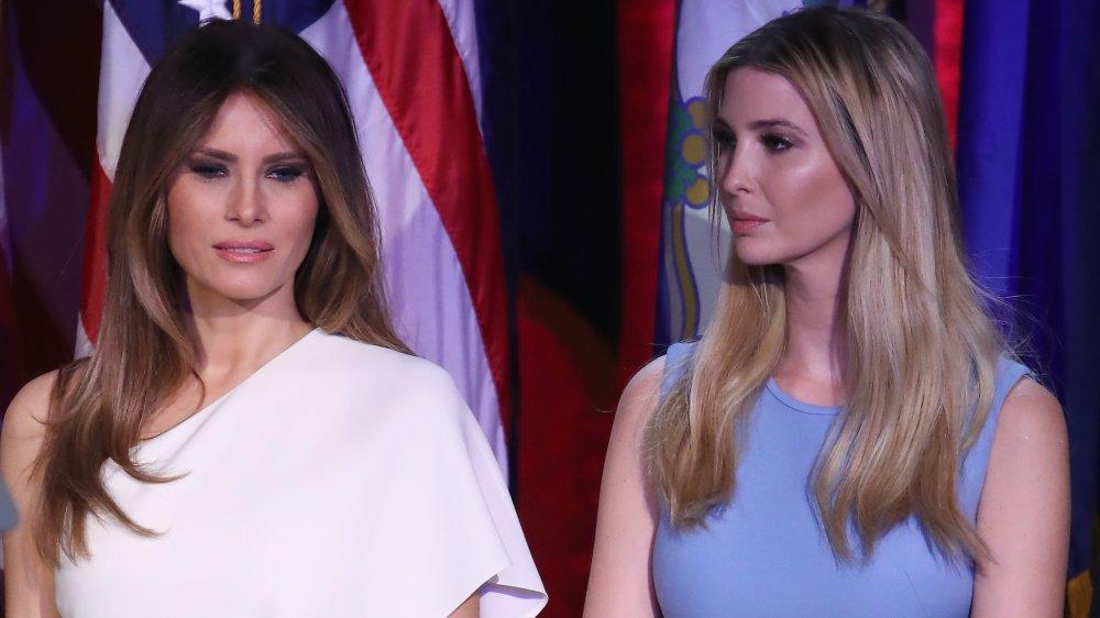 Melania Trump con un vestido blanco, Ivanka Trump con un vestido azul, de pie uno al lado del otro con expresiones serias