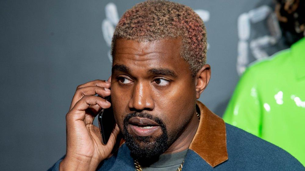 Kanye West con una chaqueta azul y marrón, hablando por teléfono