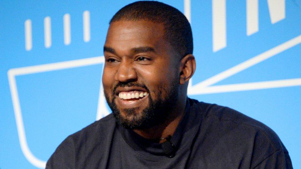 Kanye West con una camisa azul oscuro, sonriendo grande durante una entrevista