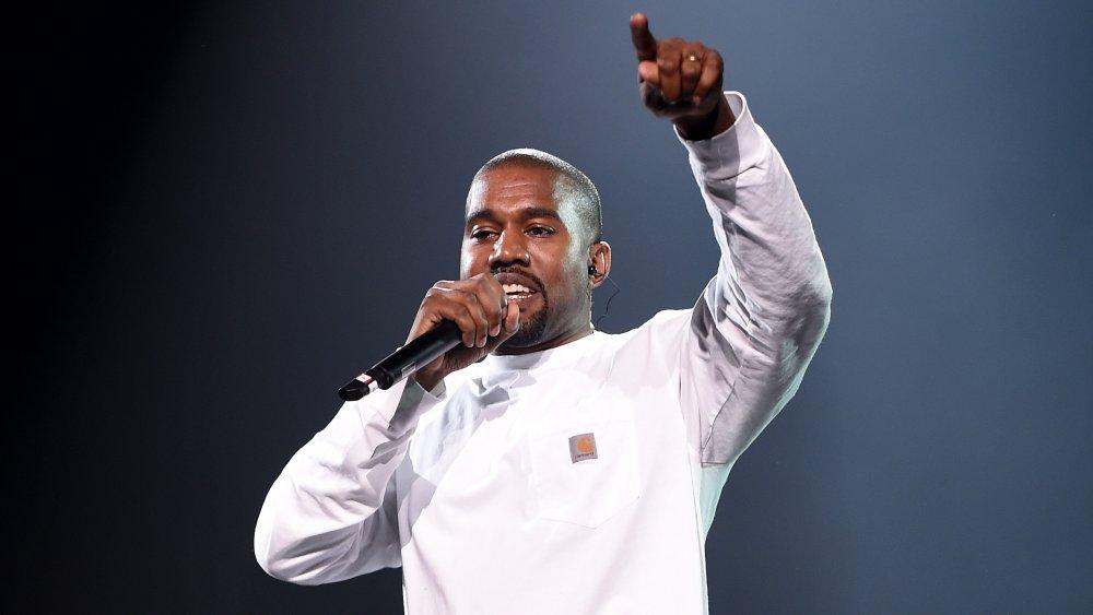 Kanye West con una camisa blanca de manga larga, actuando durante un concierto