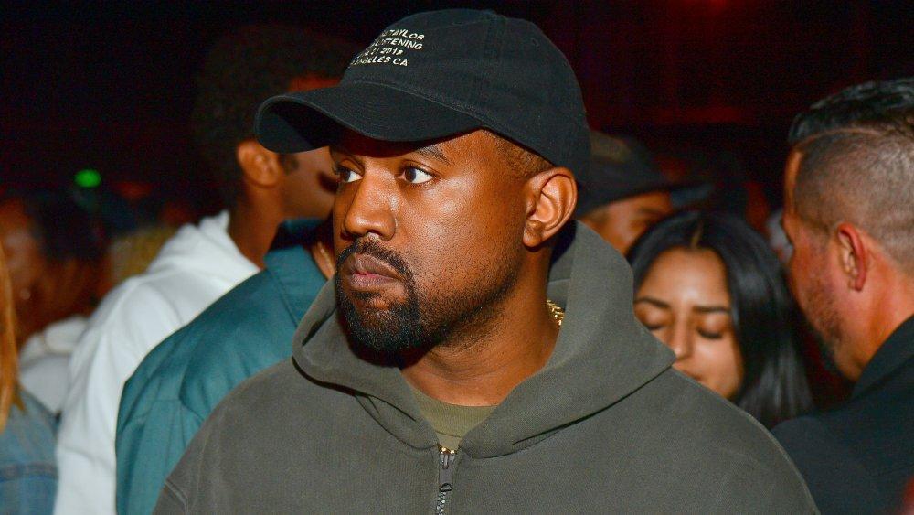 Kanye West en una sudadera con capucha gris y sombrero negro, con una expresión seria en un evento