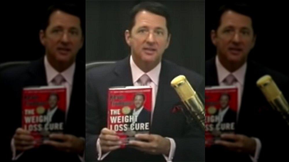 Kevin Trudeau sosteniendo una copia de su libro The Weight Loss Cure