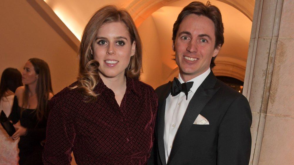 La princesa Beatriz con un traje marrón, Edoardo Mapelli Mozzi con un esmoquin negro, ambos sonriendo en un evento