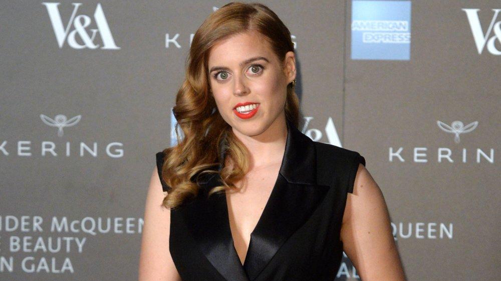 La princesa Beatriz con un vestido negro y lápiz labial rojo, sonriendo en un evento
