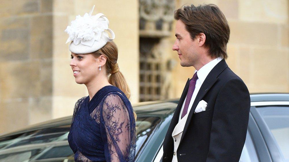 La princesa Beatriz con un vestido azul y un sombrero blanco, caminando mientras Edoardo Mapelli Mozzi observa