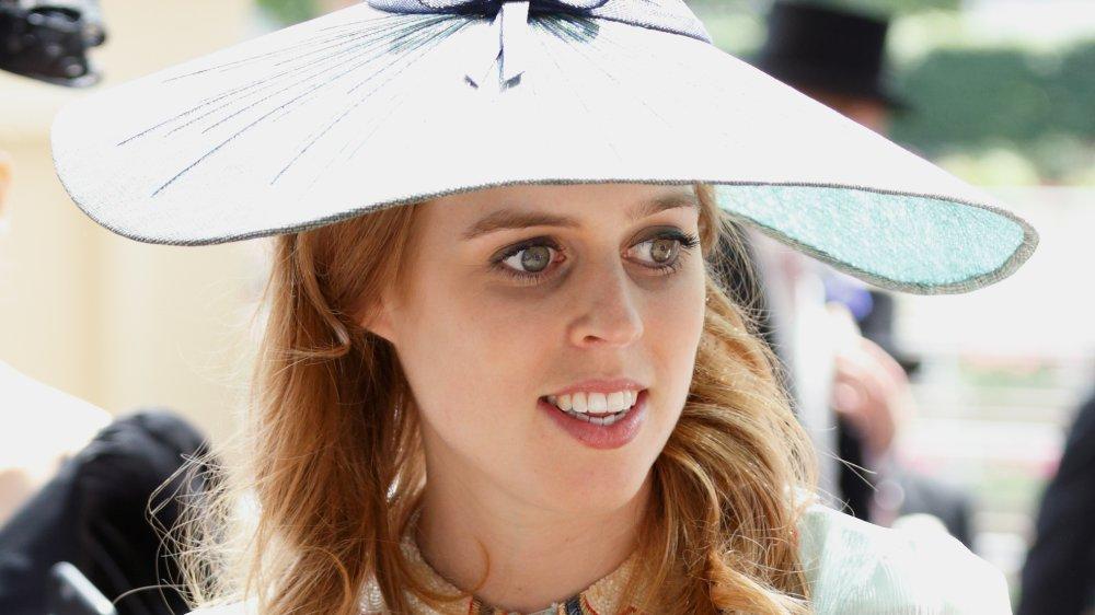 La princesa Beatriz con un traje blanco y un sombrero grande, mirando hacia un lado mientras sonríe