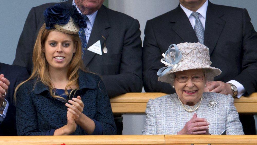 La princesa Beatriz con un traje azul oscuro y un sombrero, la reina Isabel con un traje azul claro, aplaudiendo y sonriendo