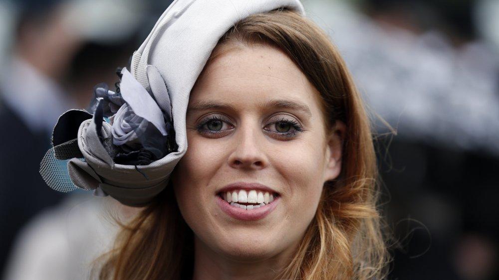 La princesa Beatriz sonríe con un sombrero de color morado claro y mira directamente a la cámara.