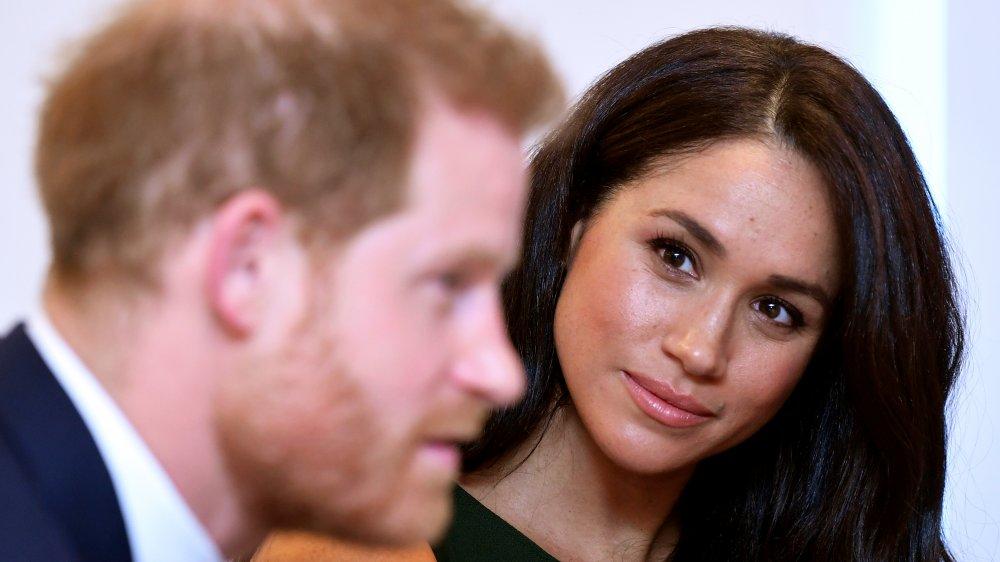 Príncipe Harry hablando con Meghan Markle detrás de él