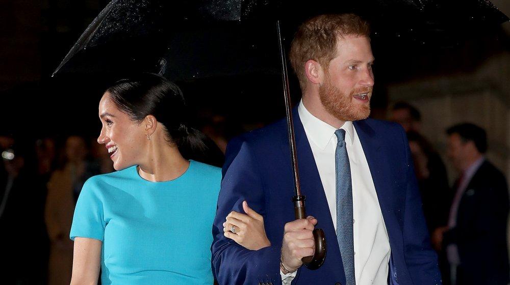 Meghan Markle y el príncipe Harry bajo un paraguas