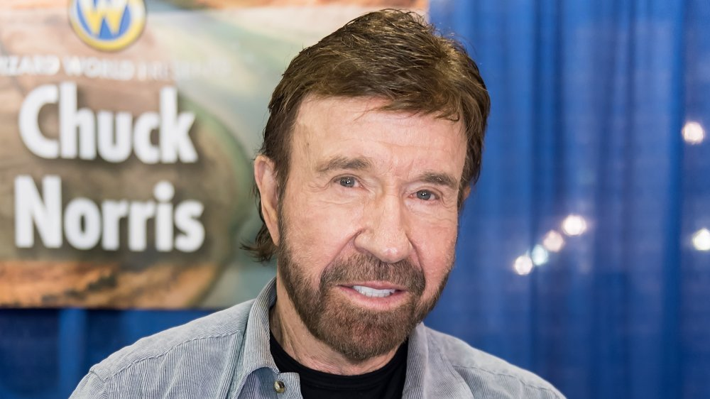 Chuck Norris sonriendo frente al cartel de Chuck Norris