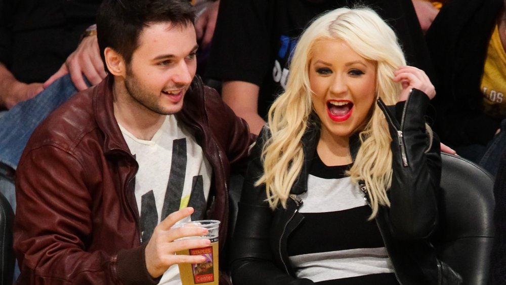 Matthew Rutler and Christina Aguilera sitting courtside at a Lakers game in 2012