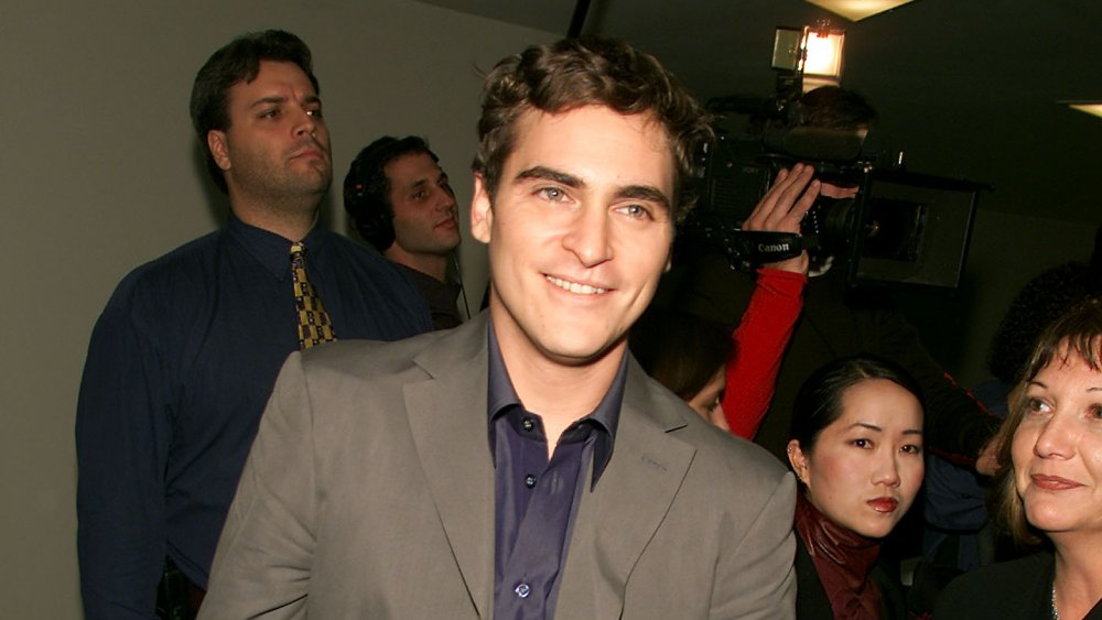 Joaquin Phoenix in a dark beige suit and blue shirt, smiling at a museum event in 2000