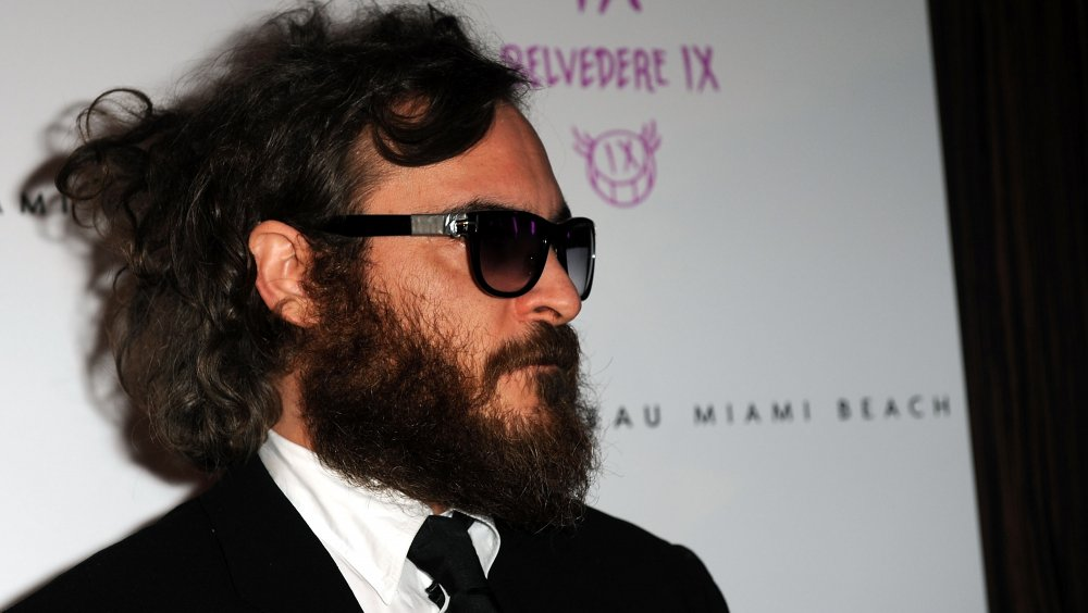 Joaquin Phoenix in a black suit, beard, and sunglasses in 2009