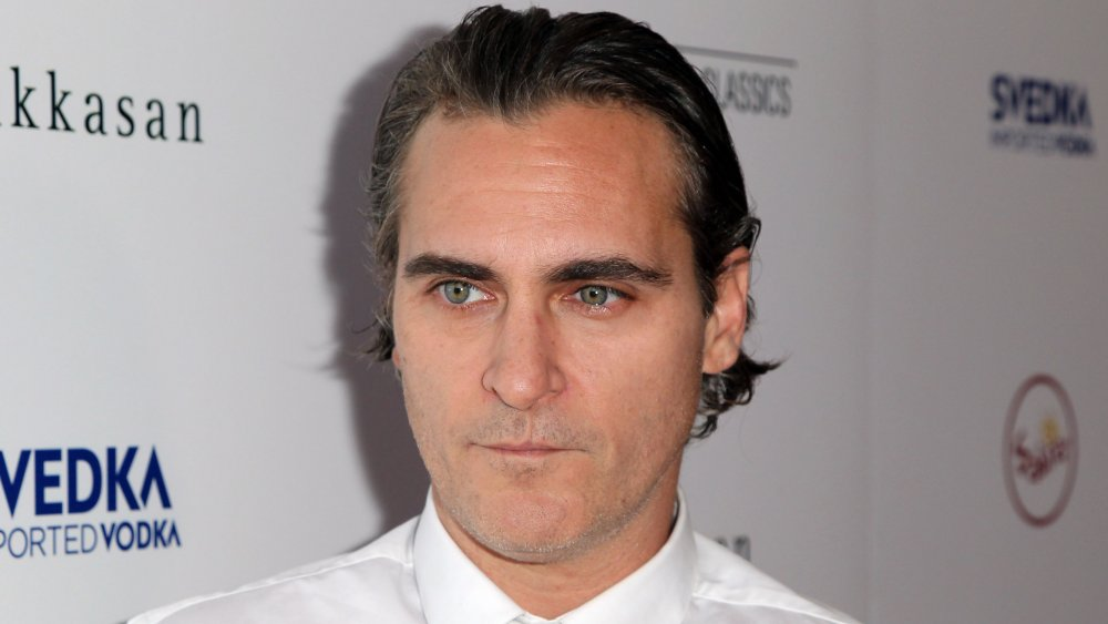 Joaquin Phoenix with slicked-back hair, in a white shirt and tie, looking serious