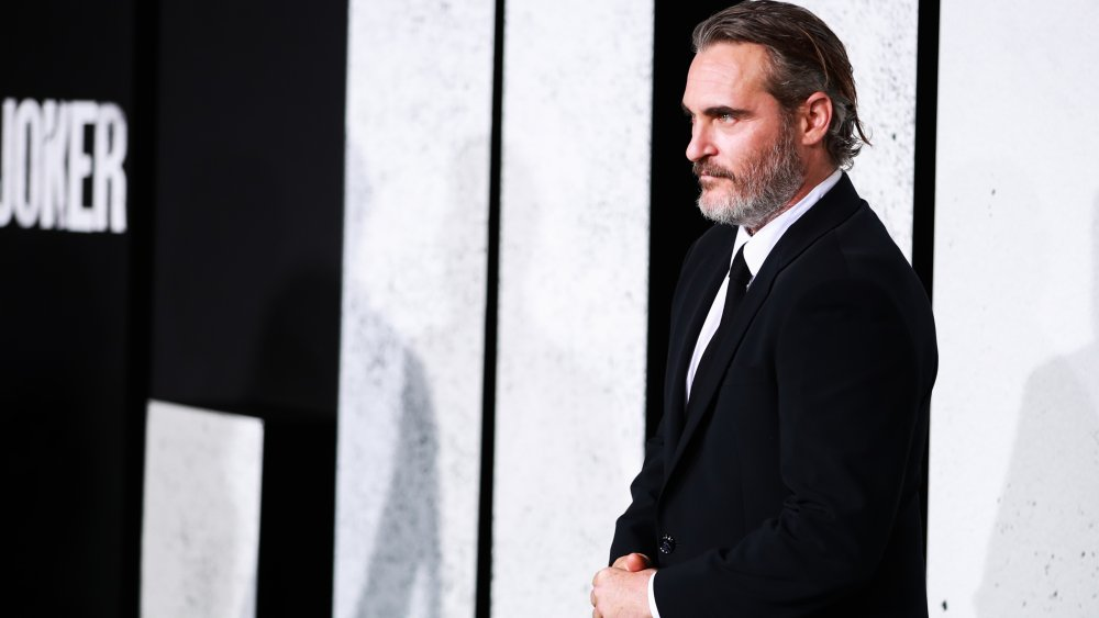 Joaquin Phoenix facing photographers in a black suit at the Joker premiere in 2019