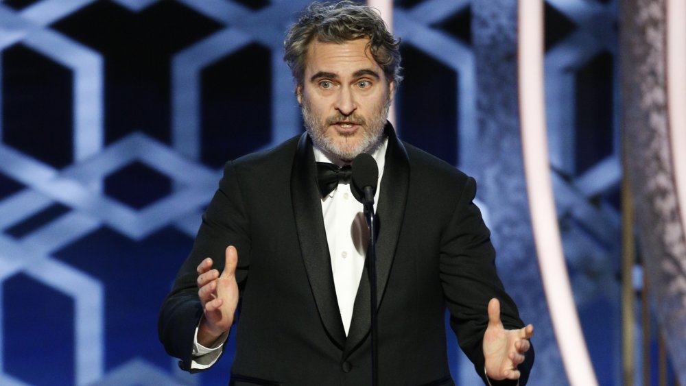Joaquin Phoenix speaking while gesturing with his hands at the 2020 Golden Globes