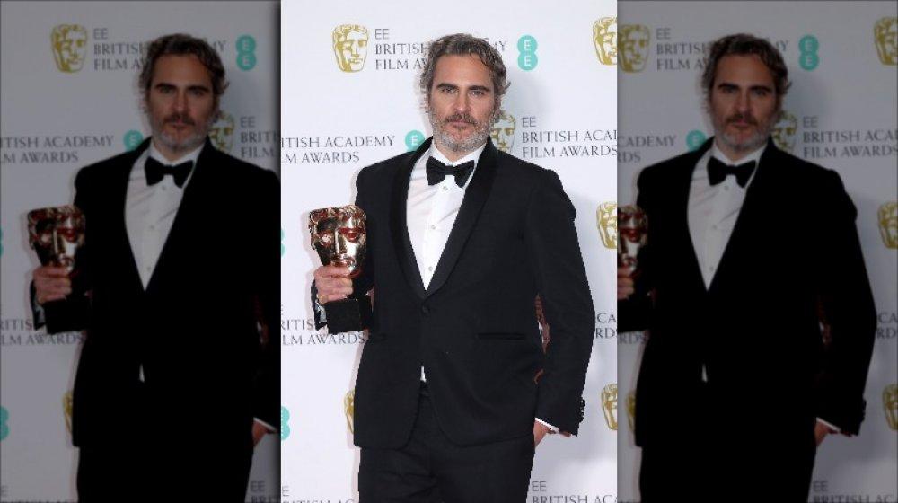 Joaquin Phoenix holding his BAFTA award in 2020