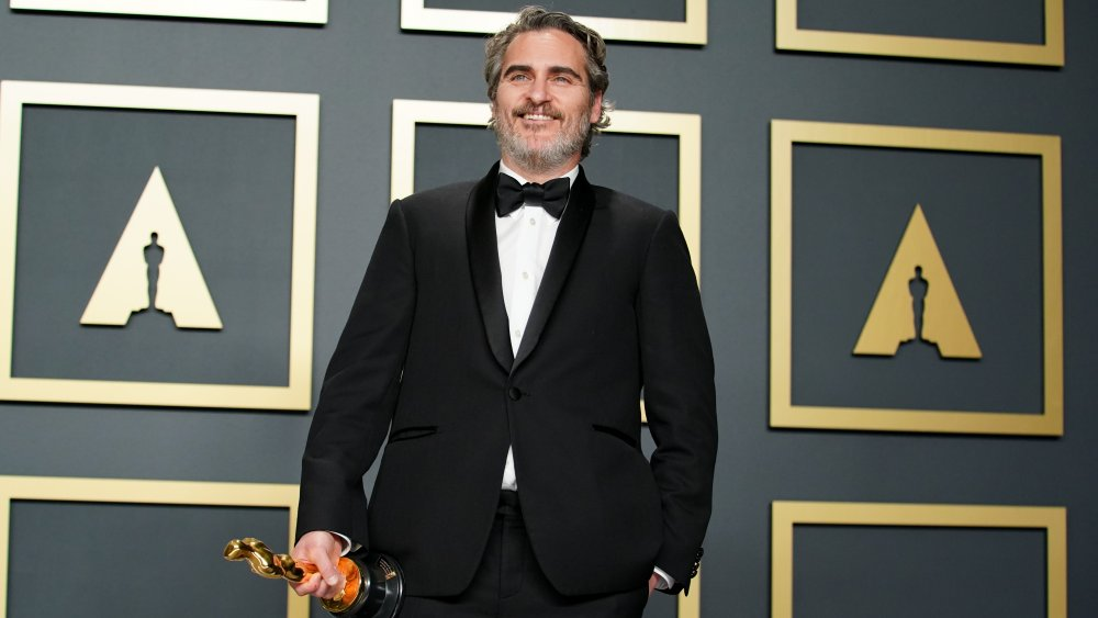 Joaquin Phoenix smiling while holding his Oscar award in 2020