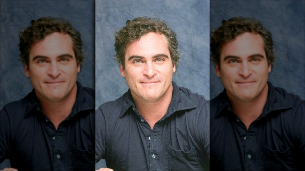 Joaquin Phoenix in a dark button-up shirt, posing with a small smile