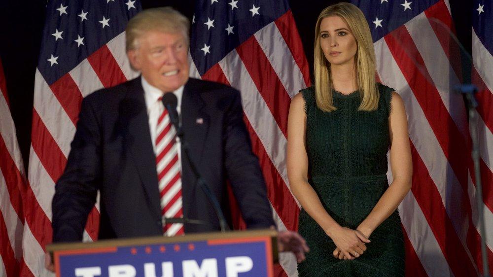 Ivanka Trump con un vestido verde, viendo a Donald Trump dar un discurso de campaña
