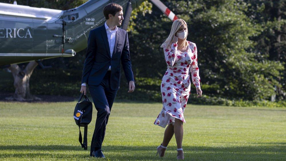 Jared Kushner en traje azul, Ivanka Trump con un vestido floral blanco y máscara facial, caminando fuera
