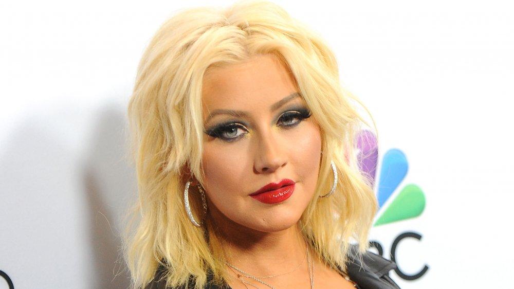 Christina Aguilera con una chaqueta de cuero negro y pendientes de aro plateado, mirando a la cámara con una expresión seria