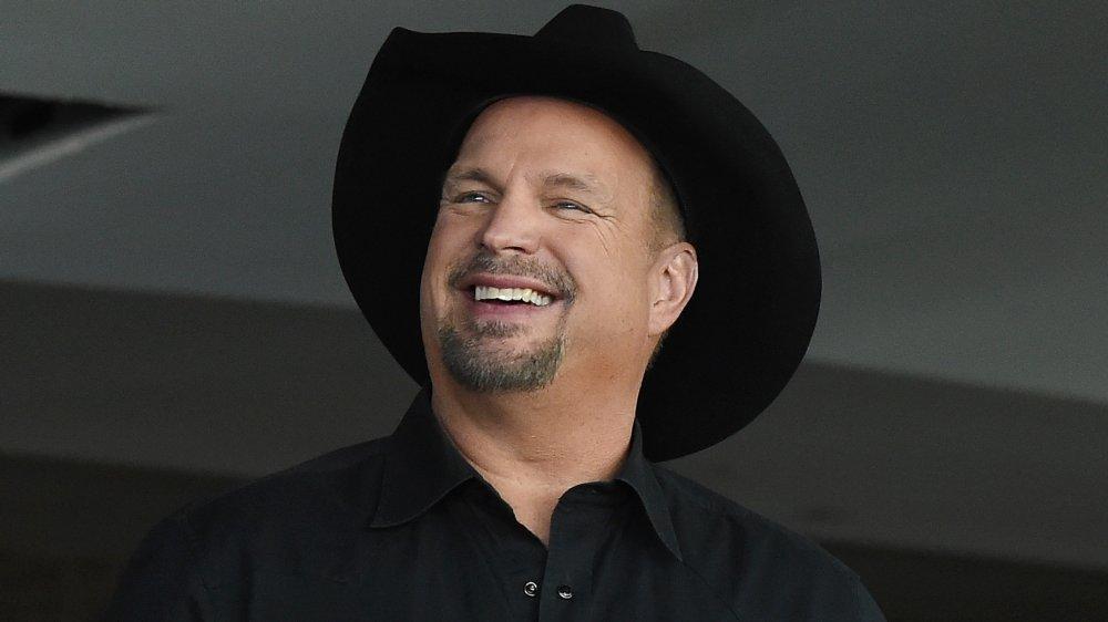 Garth Brooks con una camisa negra abotonada y sombrero de vaquero, sonriendo mientras mira hacia un lado
