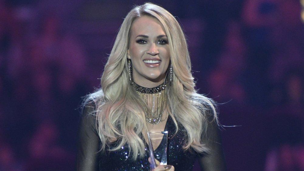 Carrie Underwood con un traje negro brillante, sonriendo mientras acepta un premio
