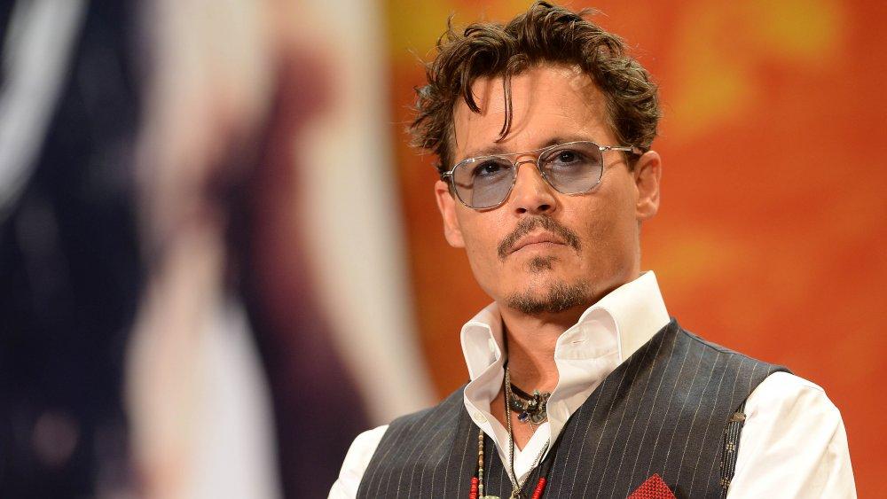 Johnny Depp con camisa blanca, chaleco gris y gafas de sol teñidas de gris