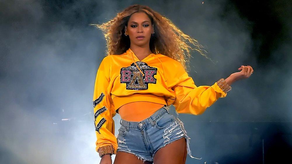 Beyoncé con sudadera amarilla con capucha y pantalones cortos de jean, actuando en Coachella 2018