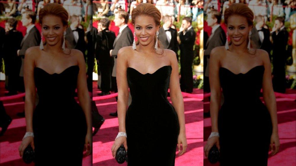 Beyoncé sonriendo con un vestido de terciopelo negro en los Oscar de 2005