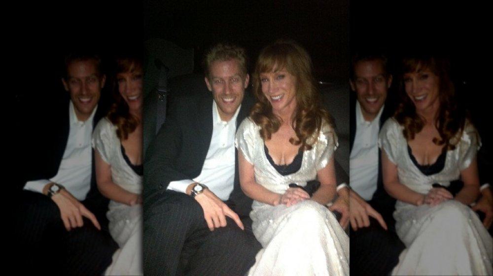 Randy Bick con un traje negro, Kathy Griffin con un vestido blanco, sentado en un coche y sonriendo juntos