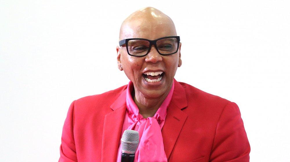 RuPaul riendo con traje rojo y rosa