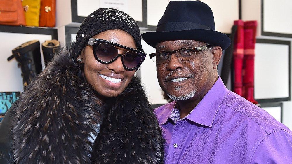 NeNe Leakes en un abrigo negro y marrón, sombrero y gafas de sol, y Gregg Leakes en una camisa púrpura y sombrero negro