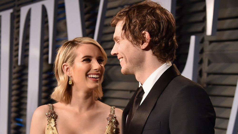 Emma Roberts con un vestido dorado y Evan Peters con un traje negro, sonriendo el uno al otro en la alfombra roja