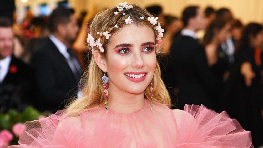 Emma Roberts con un vestido rosa y corona de flores, sonriendo