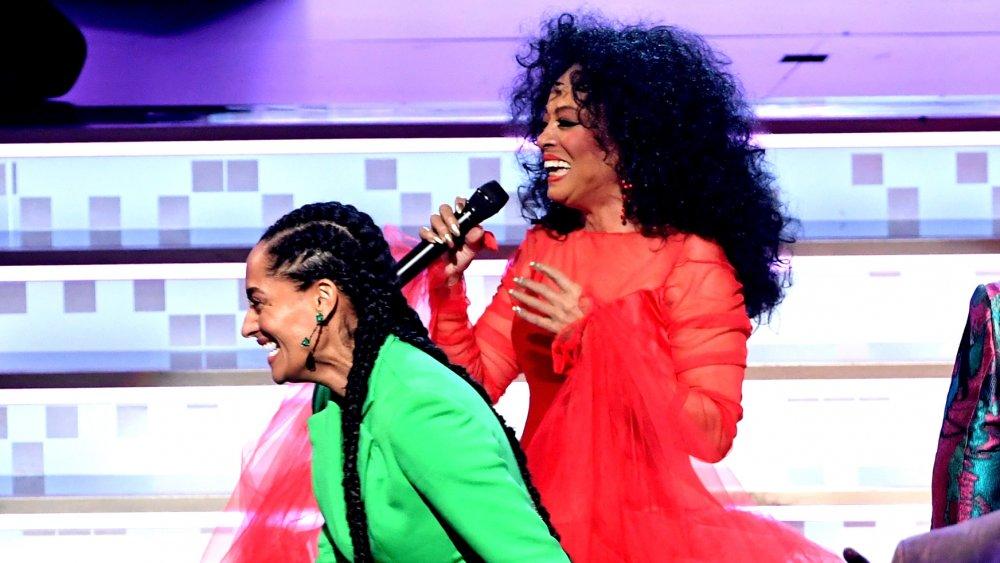 Tracee Ellis Ross con traje verde, Diana Ross con un vestido rojo, ambos riendo en el escenario en los Grammy 2019