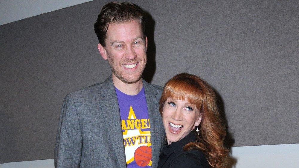 Randy Bick con una chaqueta gris y camiseta púrpura, Kathy Griffin con un traje negro, ambos sonriendo